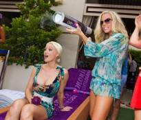 Kendra Wilkinson-Baskett shoots T-shirts to the crowd with Holly Madison watching.