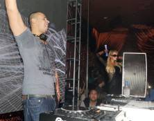 Afrojack spins at Surrender with Paris Hilton dancing nearby.