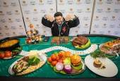 Adam Richman at the Bally's Las Vegas press conference behind a poker table filled with items representing each of the seven food-category competitions at the WFC.