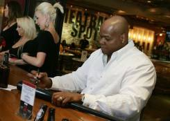 Frank Thomas signs memorabilia for fans on Meatball Spot's patio.