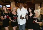 Frank Thomas shows off Big Hurt MVP Beer with promotional models at Meatball Spot.