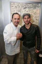 "Ryan Guzman poses with executive chef Barry S. Dakake of N9NE Steakhouse inside Palms Casino Resort after signing celebrity ""Shakedown Door."""