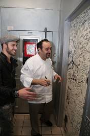 "Ryan Guzman prepares to sign executive chef Barry S. Dakake's celebrity ""Shakedown Door"" at N9NE Steakhouse."