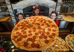 It takes three Pin-Up Pizza girls to hold up a 30-inch pepperoni pizza pie.