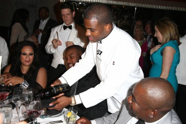 Chris Paul serving his guests wine