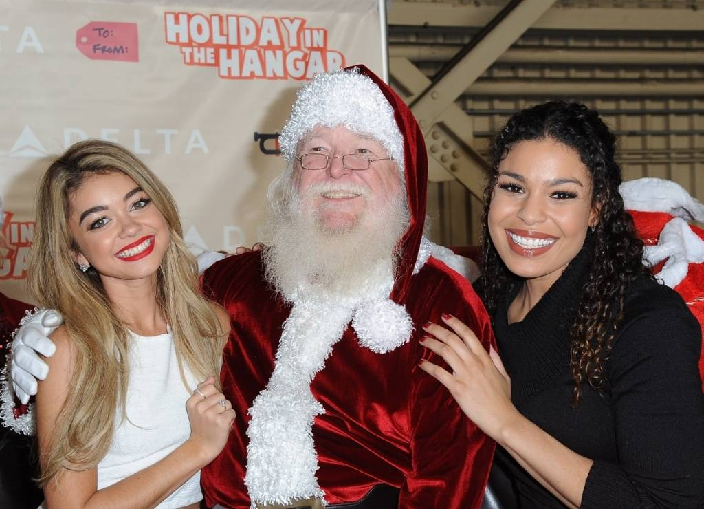 Sarah Hyland and Jordin Sparks pose with Santa at Delta Air Lines' Fourth Annual Holiday in the Hangar